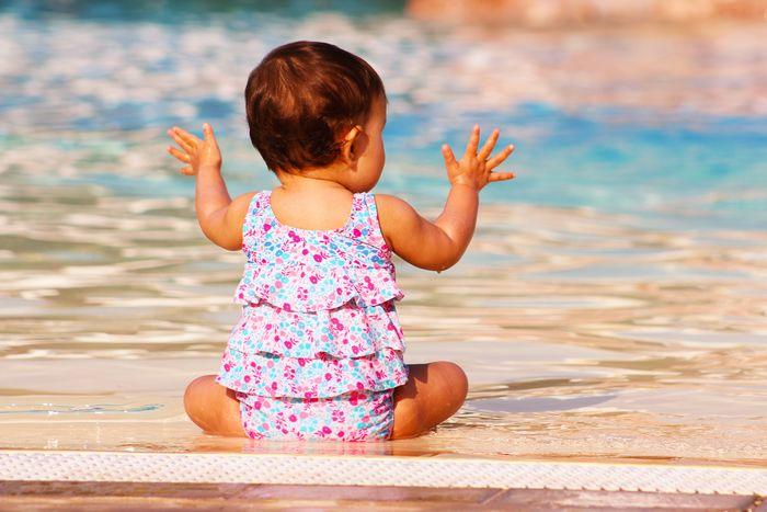 bébé assis au bord de la piscine